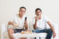 Hommes observant le jeu de sport à la TV ensemble Images libres de droits