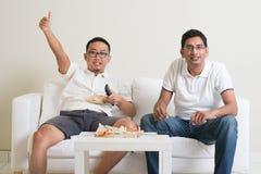 Hommes observant le jeu vivant de sport à la TV à la maison Photographie stock libre de droits