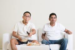 Hommes observant le jeu vivant de sport à la TV ensemble Photo stock
