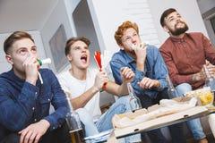 Hommes observant le sport sur encourager d'esprit d'équipe de TV ensemble à la maison Photographie stock libre de droits