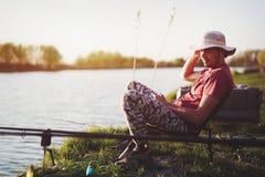 Hommes pêchant dans le coucher du soleil et détendant tout en appréciant le passe-temps Photo stock