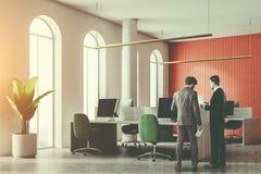 Hommes parlant dans le bureau blanc et rouge de l'espace ouvert Photo stock