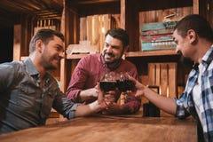 Hommes positifs beaux détendant dans le bar Image libre de droits