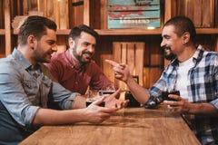 Hommes positifs gais agissant l'un sur l'autre les uns avec les autres Images stock