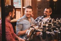 Hommes positifs gais s'asseyant au compteur de barre Image libre de droits