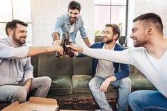 Hommes positifs joyeux faisant tinter des bouteilles Images stock