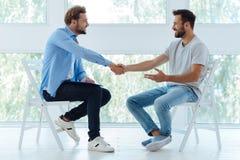 Hommes positifs joyeux se serrant la main Image libre de droits