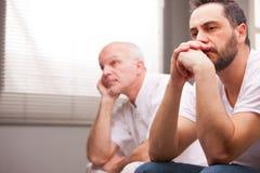 Hommes préoccupés par quelque chose dans un salon Image stock