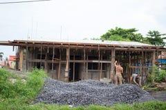 Hommes reconstruisant leur maison Photo libre de droits