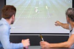 Hommes regardant la rencontre sur l'écran plat TV Photographie stock libre de droits