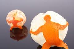 Hommes retenant l'orange et la mandarine Photographie stock libre de droits