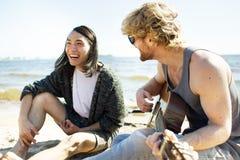 Hommes riants jouant la guitare sur la plage Photographie stock libre de droits