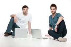 Hommes s'asseyant devant des ordinateurs portatifs Photos stock
