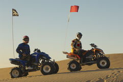 Hommes s'asseyant sur des vélos de quadruple dans le désert Images stock