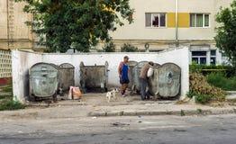 Hommes sans abri recherchant dans des restes de récipient de déchets Photo stock