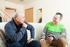 Hommes se reposant à la maison et parlant Image stock