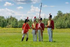 Hommes se tenant dans des manteaux militaires rouges Photos stock