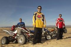 Hommes se tenant prêt des vélos de quadruple dans le désert Photographie stock