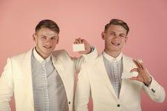 Hommes souriant avec les cartes vierges sur le fond rose Photos libres de droits