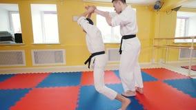 Hommes sportifs formant leurs qualifications d'aikido dans le studio Technique de protection employant le poids de l'adversaire banque de vidéos