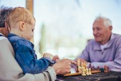 Hommes supérieurs ayant l'amusement et jouant des échecs au parc Image stock