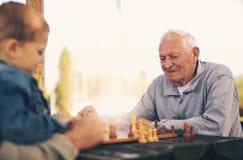 Hommes supérieurs ayant l'amusement et jouant des échecs au parc Photographie stock libre de droits