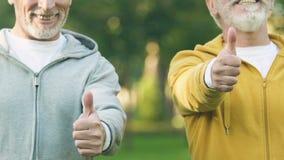Hommes supérieurs dans des costumes de sport montrant les pouces-, centre de fitness pour des retraités, santé banque de vidéos