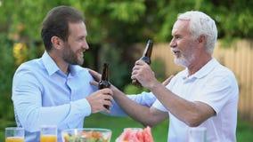 Hommes supérieurs et d'une cinquantaine d'années faisant tinter des bouteilles à bière et parlant, traditions de brassage banque de vidéos