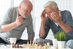 Hommes supérieurs jouant des échecs Photos stock