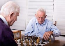 Hommes supérieurs jouant des échecs Images libres de droits