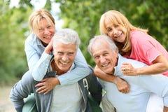 Hommes supérieurs portant leurs wifes sur rire arrière Photographie stock libre de droits