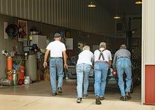Hommes supérieurs poussant la voiture calée dans le garage Images libres de droits