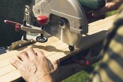 Hommes supérieurs préparant les matériaux en bois avec la scie rotatoire images stock