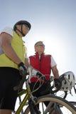 Hommes supérieurs se tenant prêt leurs bicyclettes Image stock