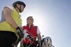 Hommes supérieurs se tenant prêt leurs bicyclettes Image libre de droits