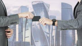 Hommes transférant une carte de crédit ou la carte de visite professionnelle de visite dans la perspective des bâtiments des grat images stock