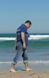 Hommes tristes marchant sur la plage Images stock