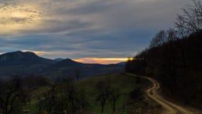 Homolje berglandskap med en slingrig gruslandsväg på solnedgången av en solig dag för höst Arkivfoton