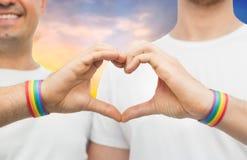 Homoseksualna para z tęcz wristbands i ręki sercem Obraz Stock