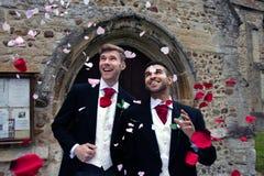 Homoseksualny ślub, fornale opuszcza wioska kościół po poślubiającego uśmiechy i confetti Obrazy Royalty Free