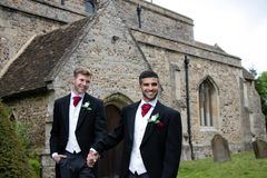 Homoseksualny ślub, fornale opuszcza wioska kościół po poślubiającego uśmiechy i confetti Zdjęcia Stock