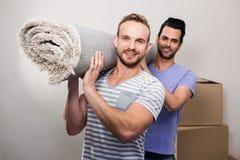 Homoseksualny pary przewożenie staczający się w górę dywanu obraz royalty free