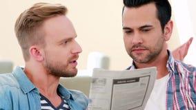 Homoseksueel paar die en krant spreken lezen stock footage