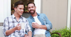 Homosexual couple drinking in a mug stock video footage