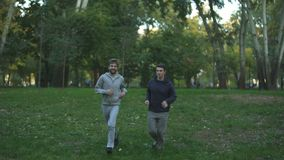 Homosexual couple jogging in park, evening training, discussing family issues stock footage