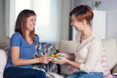 Homosexual couple of lesbian women at home on the couch celebrat. Ing a holiday and giving boxes with gifts Royalty Free Stock Photography