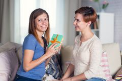 Homosexual couple of lesbian women at home on the couch celebrat. Ing a holiday and giving boxes with gifts Stock Photo