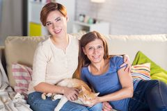Homosexual couple of lesbian women at home on the couch. With a redheaded pet cat Stock Images