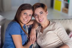 Homosexual couple of lesbian women at home on the couch hugging. And enjoying Stock Photo