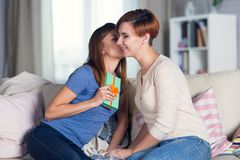 Homosexual couple of lesbian women at home on the couch celebrat. Homosexual couple of lesbian women at home on the couch kisses on the cheek celebrating a Royalty Free Stock Photos